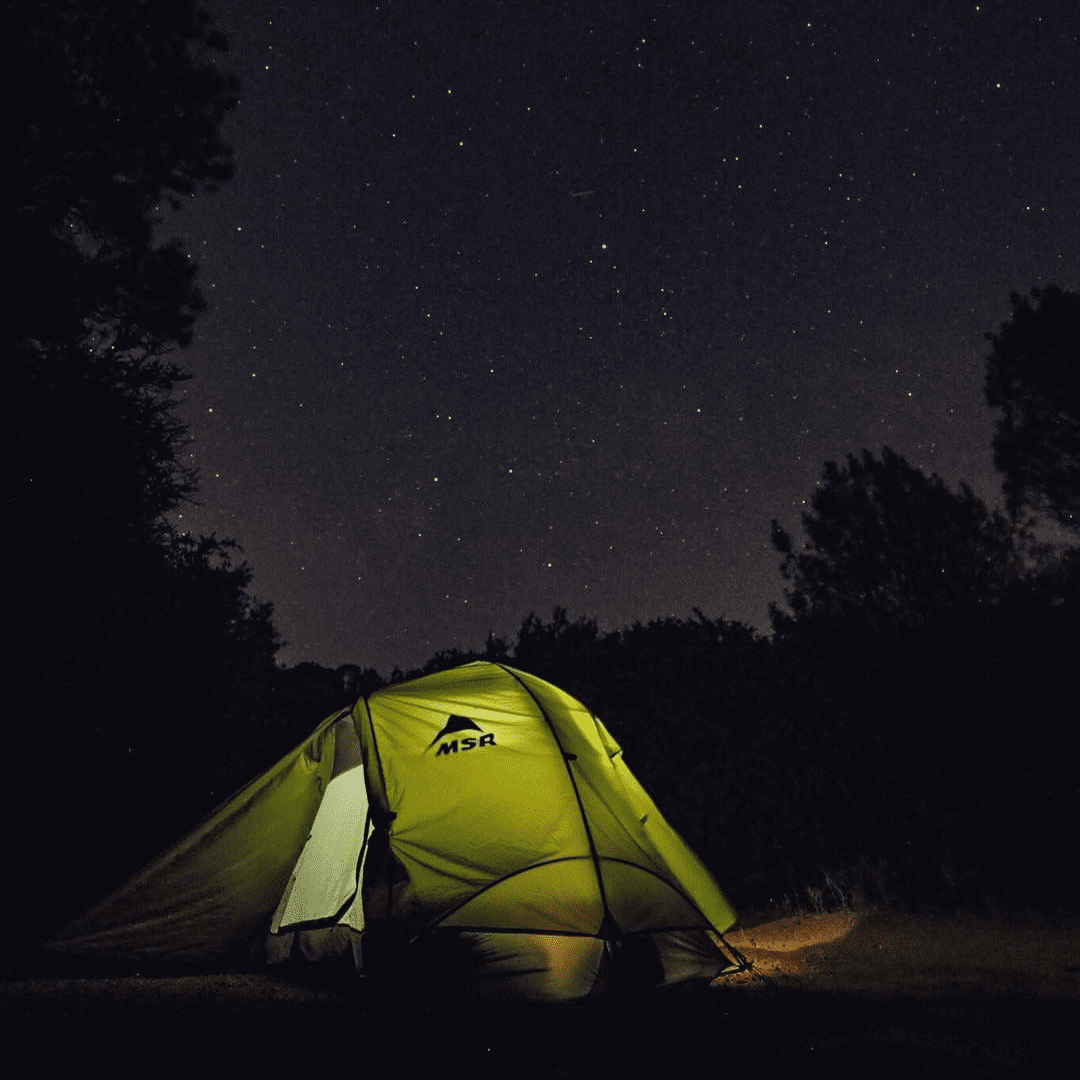 A green tent is light up from inside against a dark, starry sky behind it on Mt. Diablo State Park