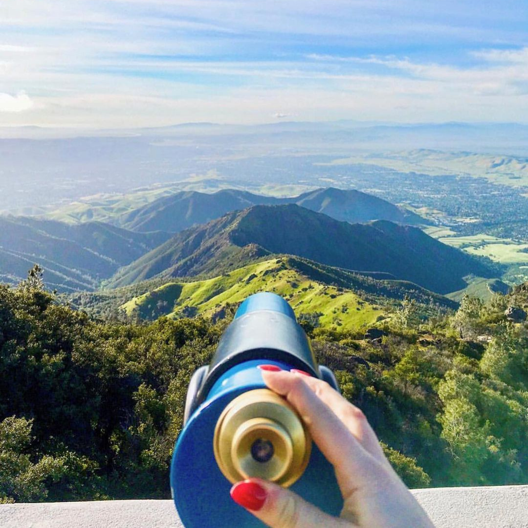 A woman's hand hold a scope that points towards green valleys and hills from Mt. Diablo State Park