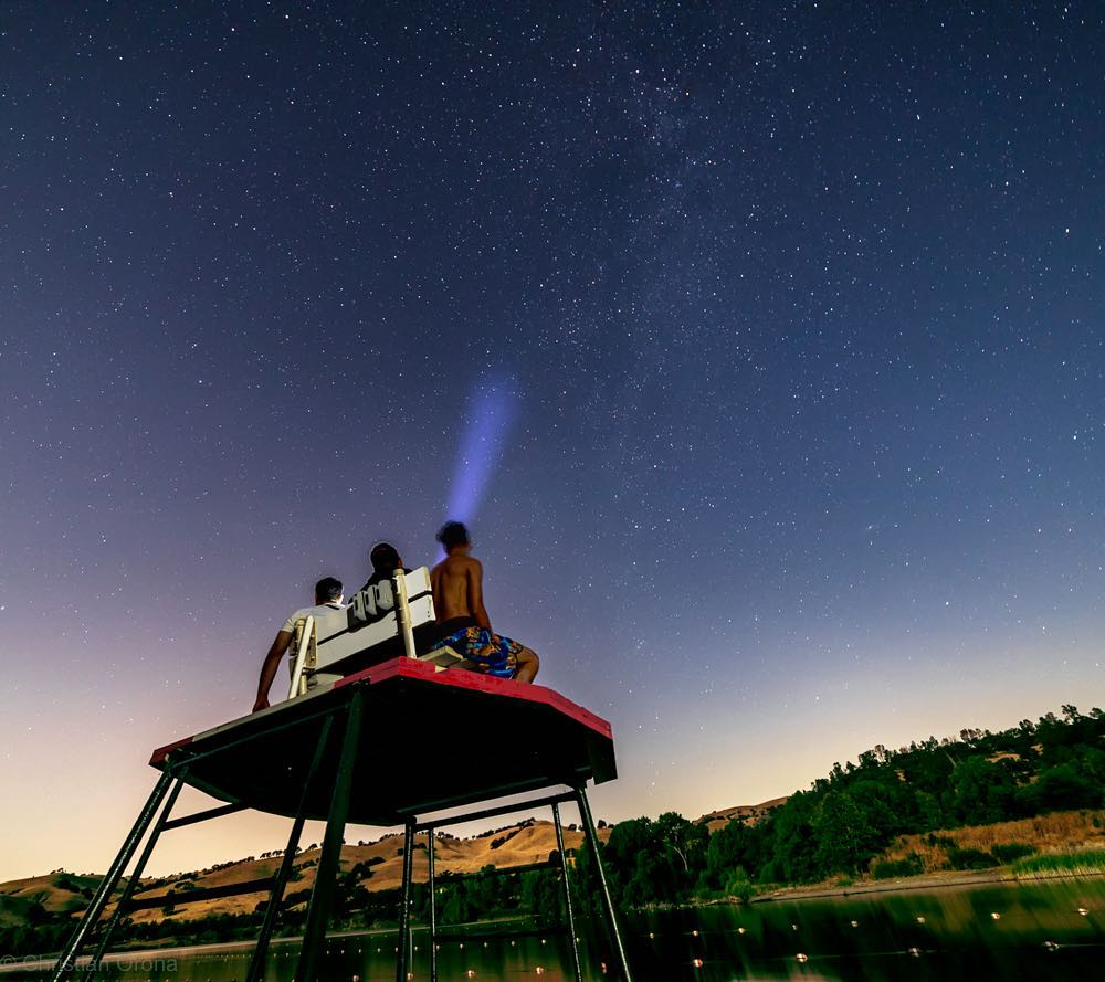 Three boys sit on top of a lifeguard stand and stare out at the dark blue skies covered in shining stars.