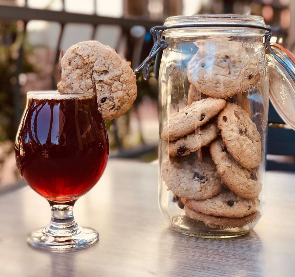 spiced beer with oatmeal cookie on the rim and a jar of cookies