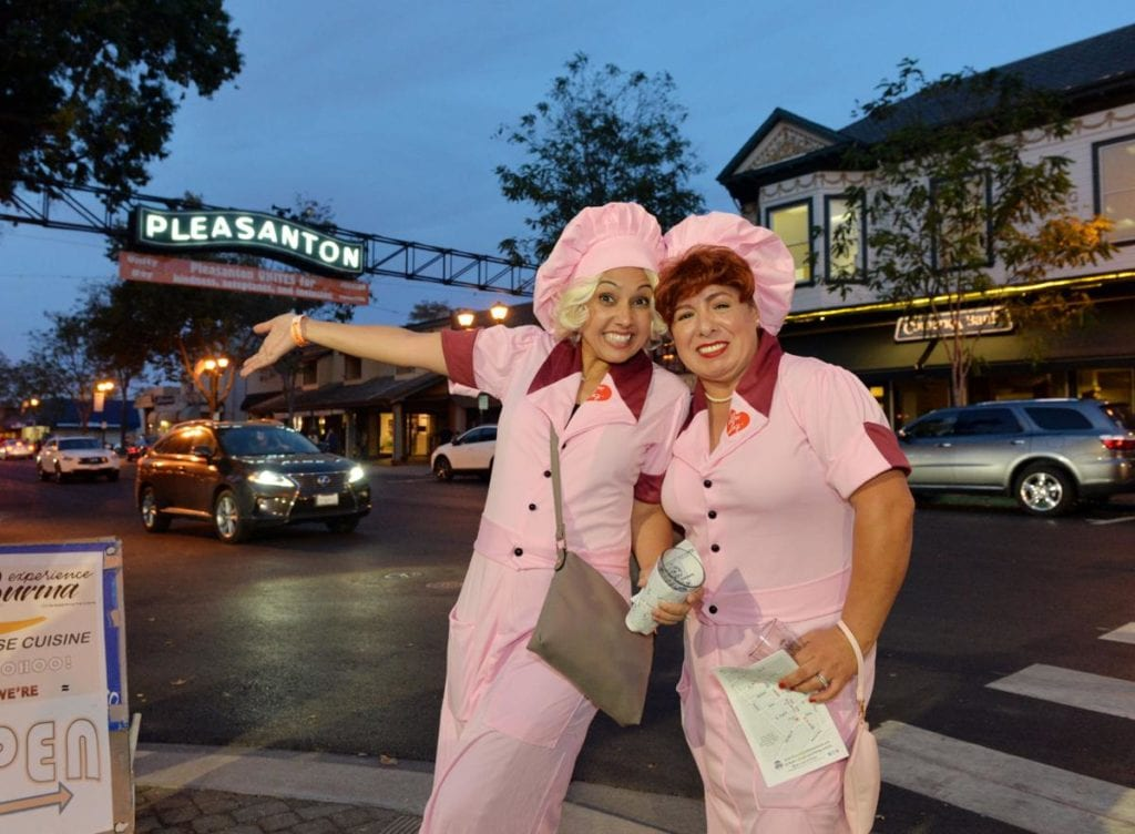 Two ladies in costume pose in front of the Downtown Pleasanton arch at Pleasanton, Ca Halloween Brew Crawl