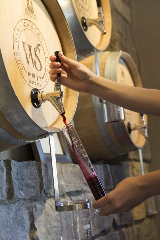 a beaker filling with wine from a barrel in the wall