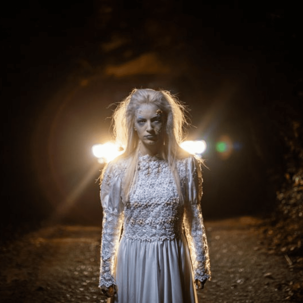 scary woman in front of car lights haunted house
